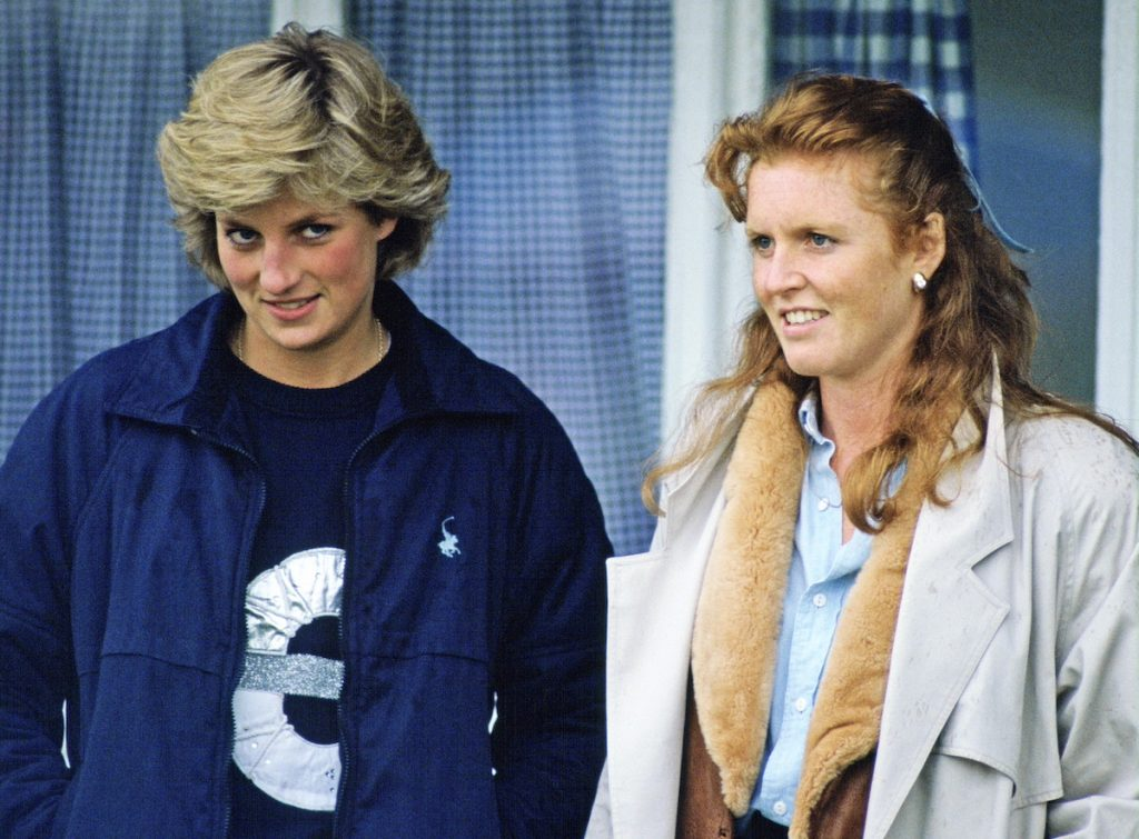 Princess Diana and Sarah Ferguson stand next to each as they watch a polo match