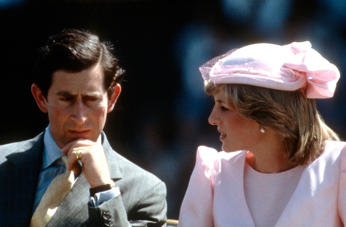 Princess Diana wearing a pink dress and fascinator while seated next to Prince Charles who looks to be in deep thought