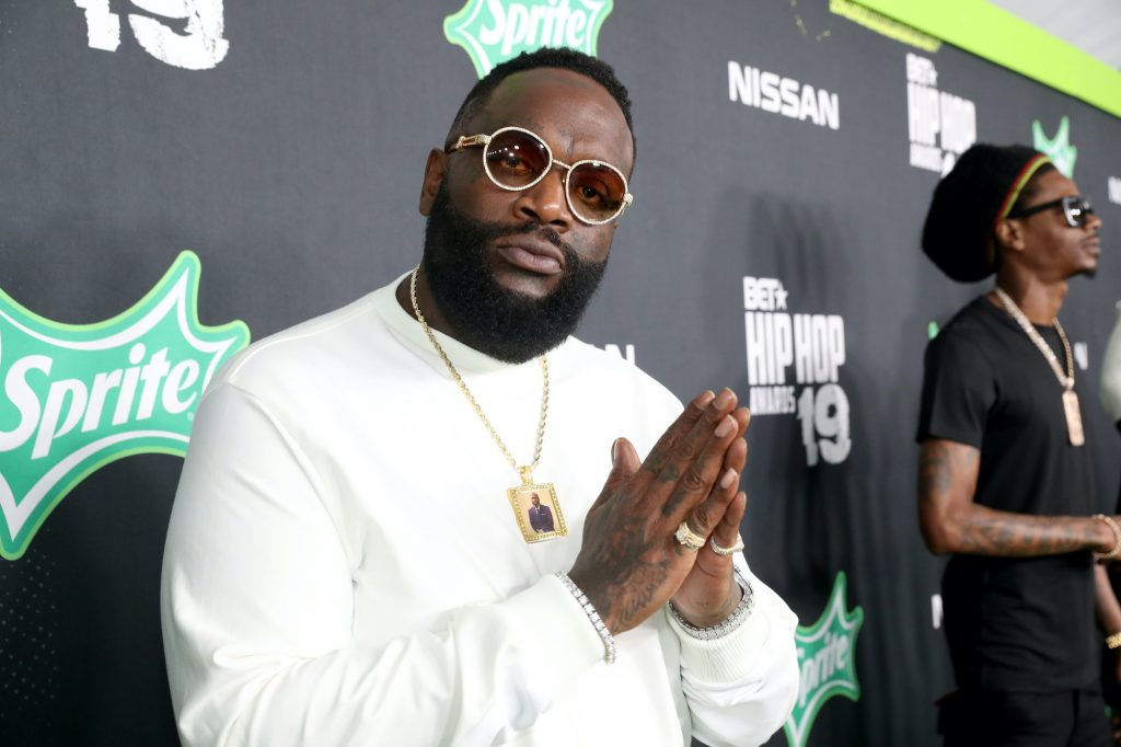 Rick Ross looking at the camera in front of a black background