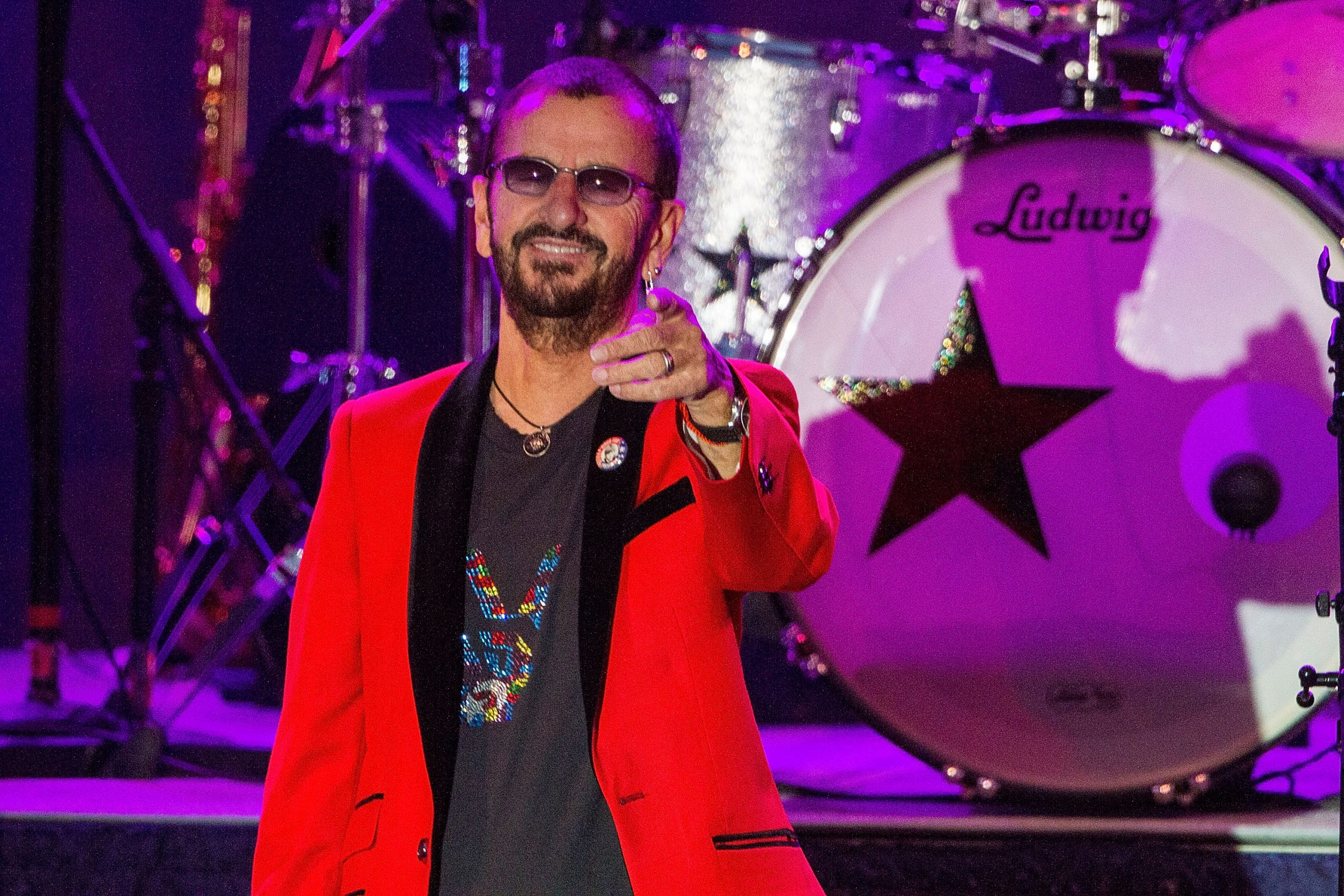 Ringo Starr wears a red jacket and T-shirt as he smiles and points out to the crowd from on stage in 2016.