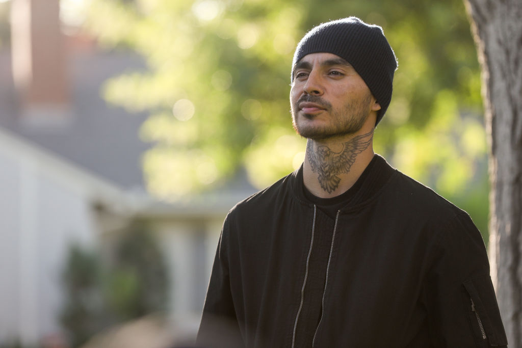 Manny Montana as Rio stands with a menacing look on his face. He's wearing a beanie and a dark jacket but his eagle tattoo is visible on his neck.