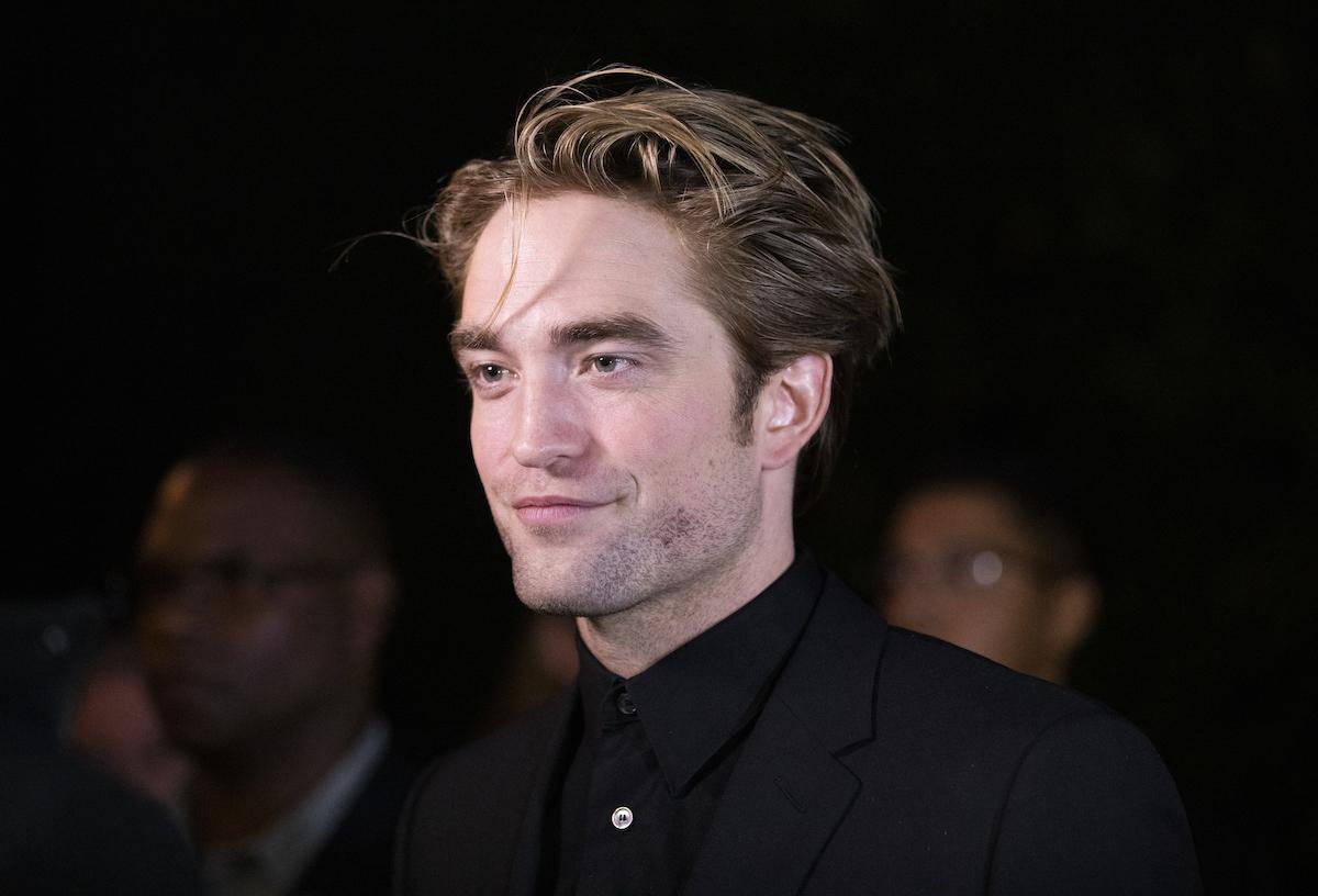 The Twilight Saga alum Robert Pattinson smirks at the camera in a black shirt