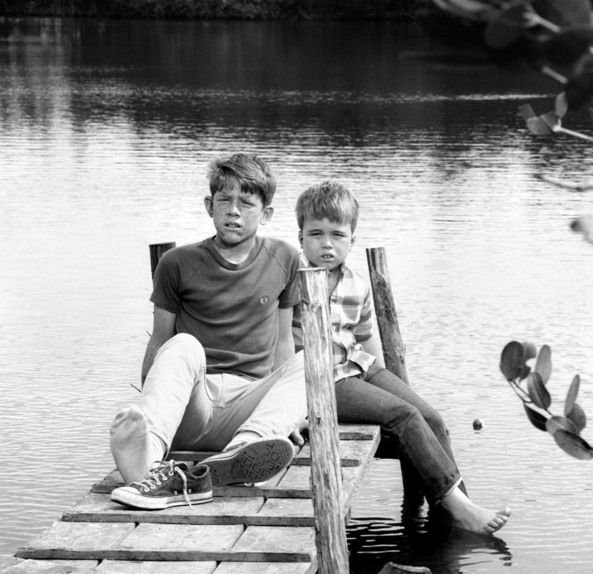 Ron and Clint Howard sit on a dock on the set of 'Gentle Ben'