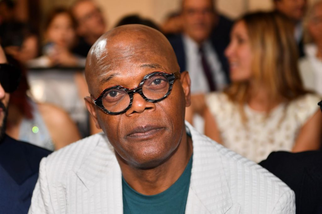 Samuel L. Jackson wearing a textured cream suit jacket with a green undershirt and black rimmed glasses in front of a background of several blurred images of people.