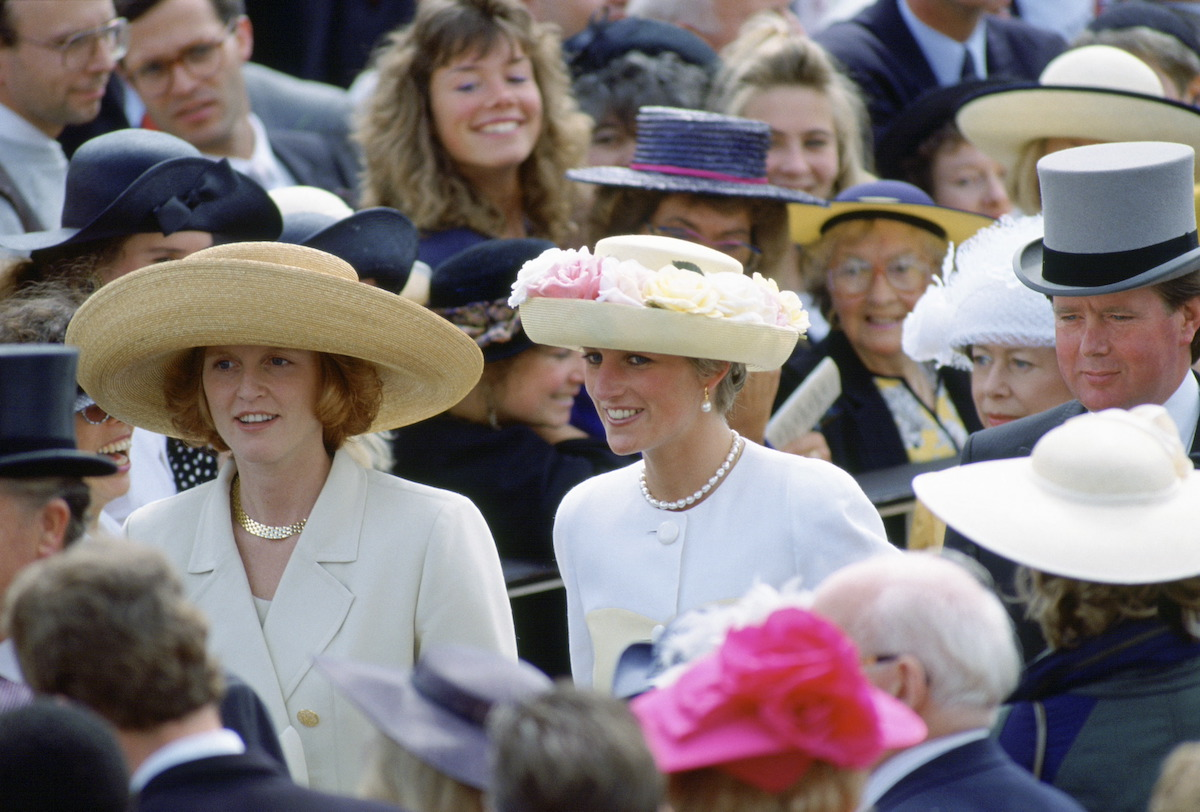 Sarah Ferguson and Princess Diana smile as they walk through the crowd at the Ascot Races