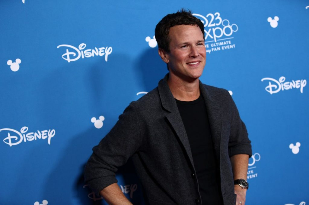 Scott Weinger, voice actor of the 1992 'Aladdin,' is standing in front of a blue backdrop with 'Disney' written in random places dressed in a black undershirt with a quarter-sleeve black suit jacket.