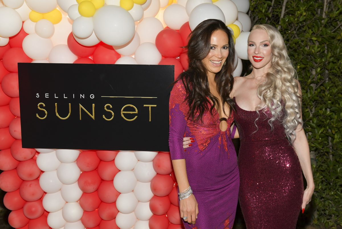 Davina Potratz (L) and Christine Quinn from 'Selling Sunset' Season 4 standing with their arms around each other next to a 'Selling Sunset' sign at a viewing party
