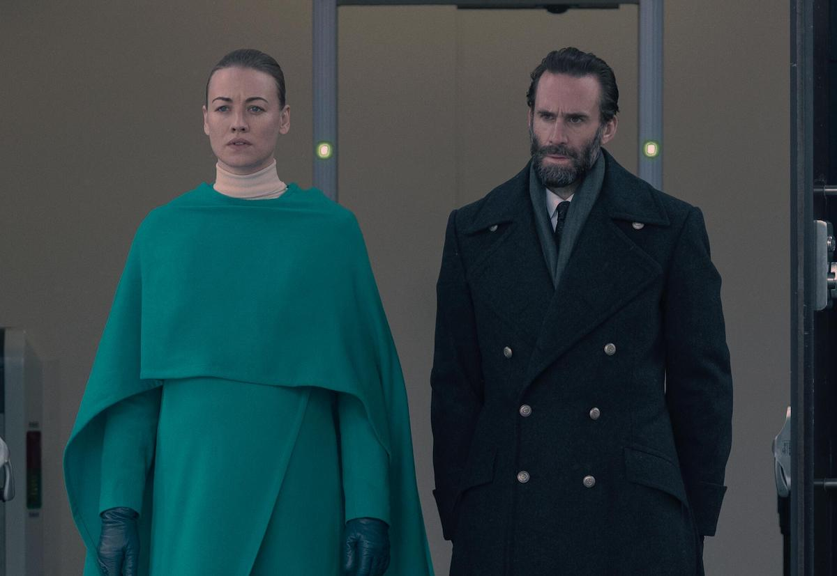 Yvonne Strahovski as Serena Joy Waterford and Joseph Fiennes as Fred Waterford in 'The Handmaid's Tale' Season 4. Strahovski wears a teal dress and coat. Fiennes wears a black wool coat and suit. They're walking out of a building with metal detectors behind them.