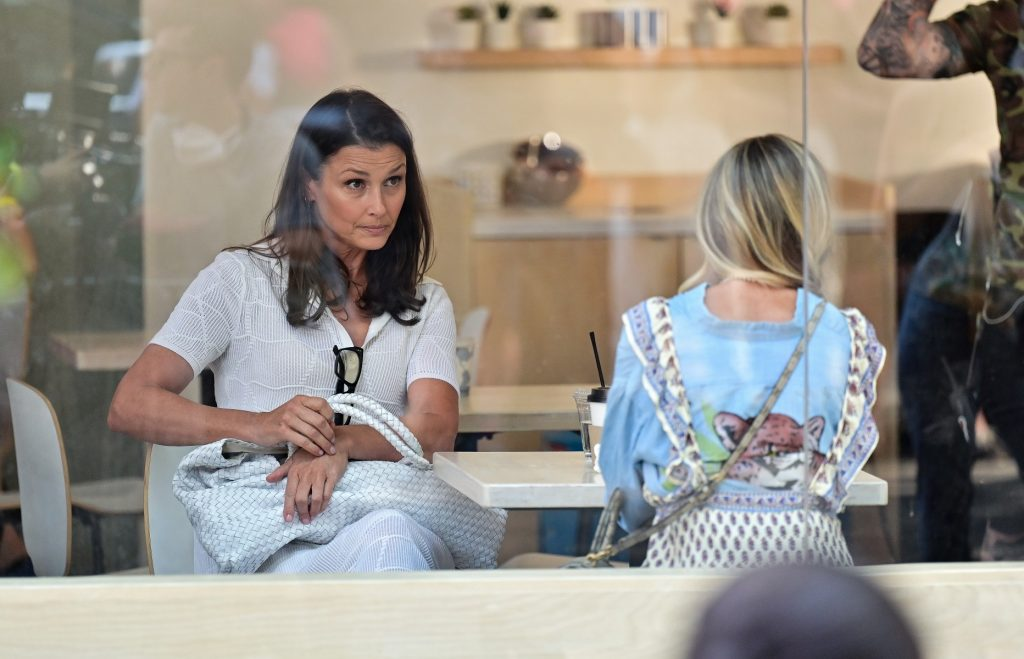 Bridget Moynahan and Sarah Jessica Parker sit together on the set of 'And Just Like That...' on July 27, 2021 in New York City