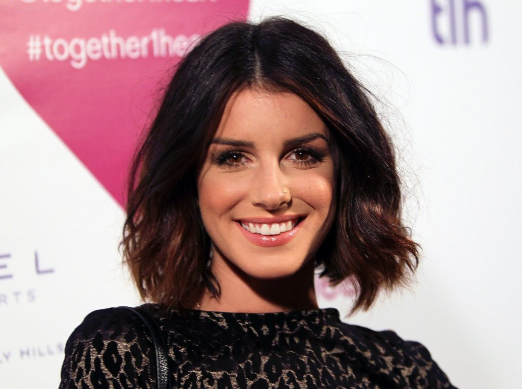 Shenae Grimes-Beech smiling in front of a white background