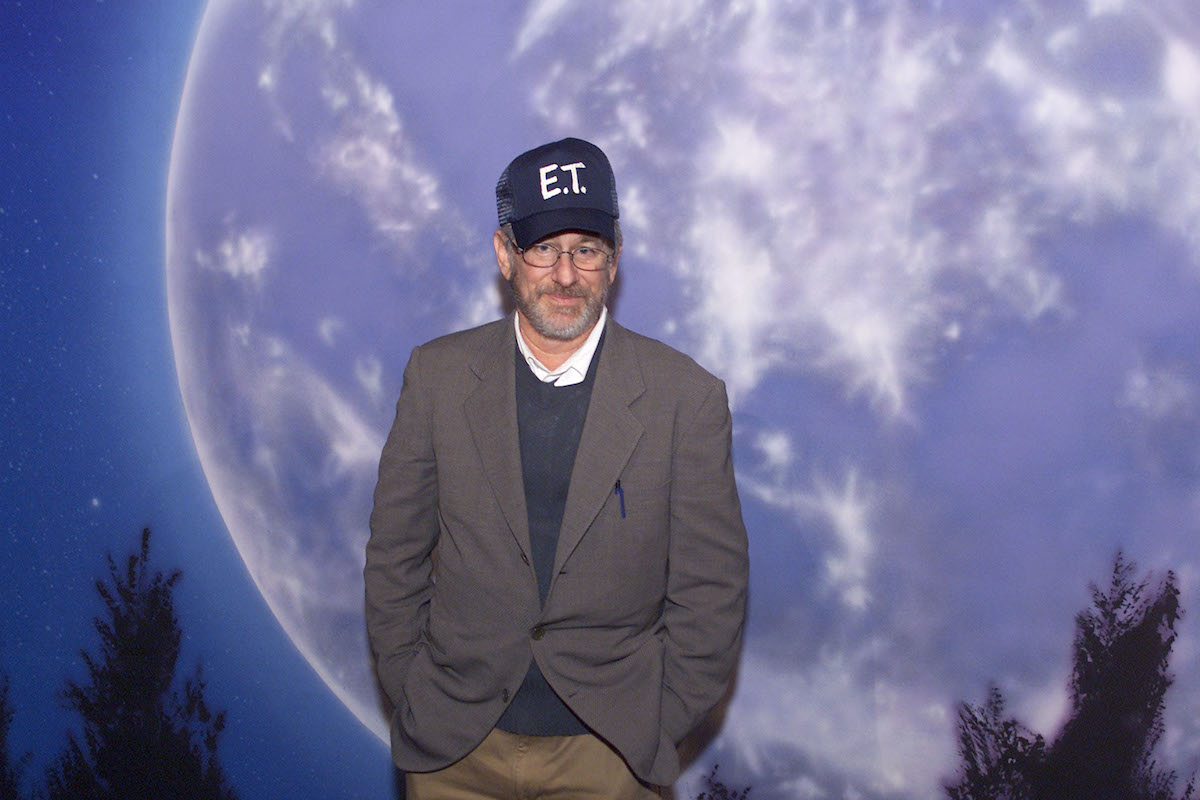 Steven Spielberg wears an 'E.T' hat and poses in front of the movie's poster