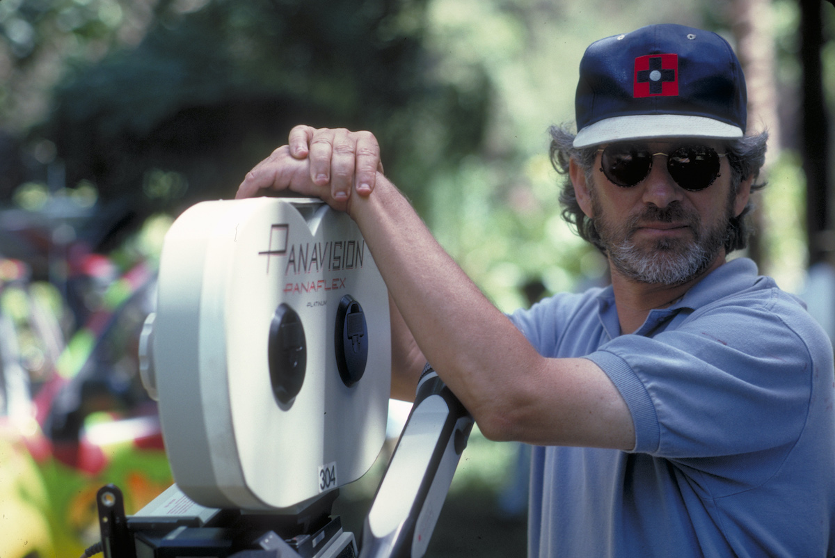 Steven Spielberg wears a hat and poses with a camera