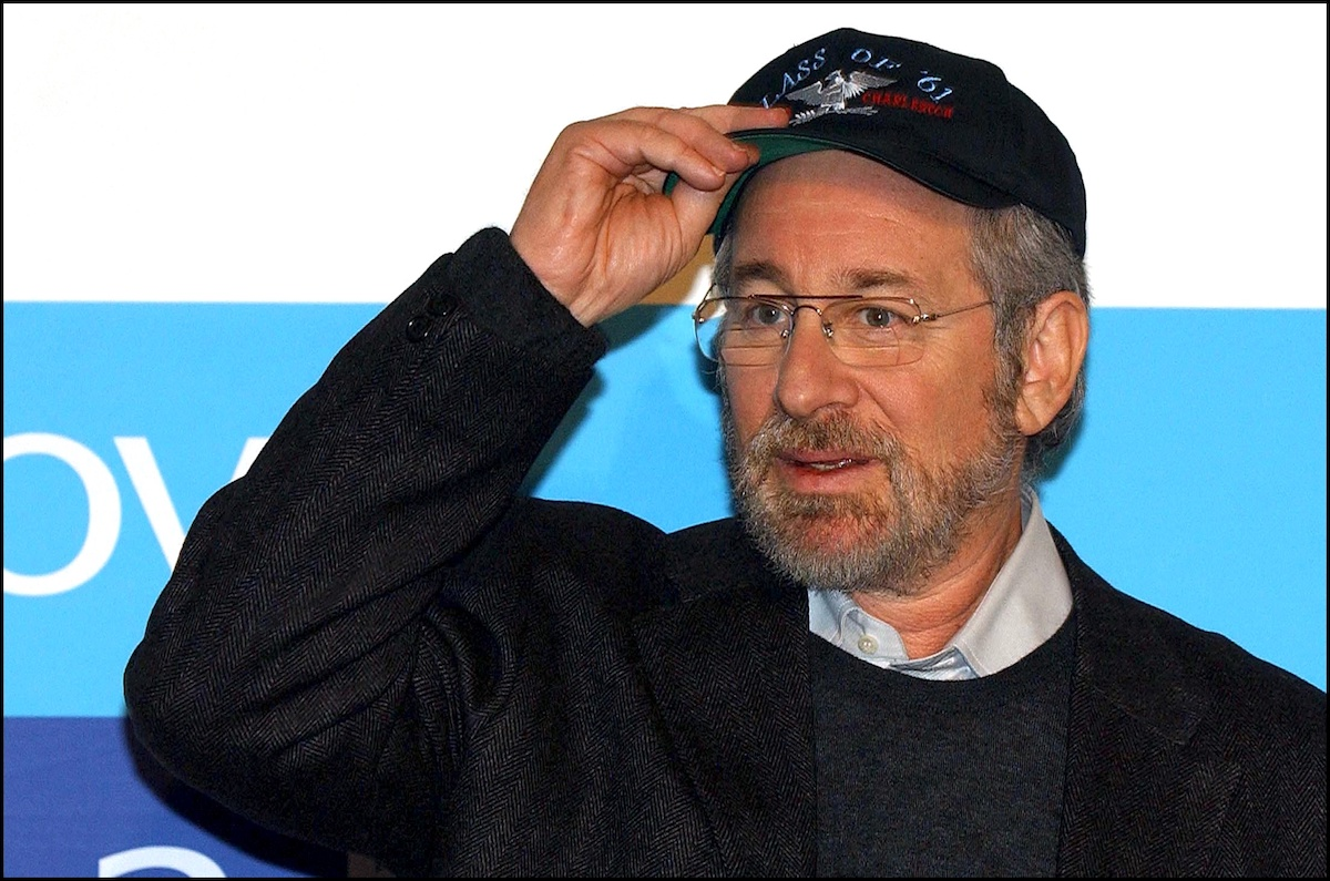 Steven Spielberg holds up his hat and looks onto the horizon