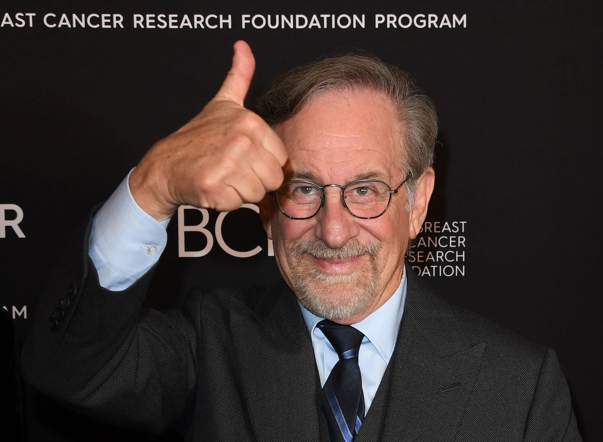 Steven Spielberg wears a suit and smiles while giving a thumbs up