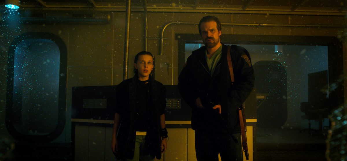Millie Bobby Brown and David Harbour as Eleven and Hopper in Stranger Things. They're standing next to one another and Eleven is dressed in black clothes with her hair slicked back