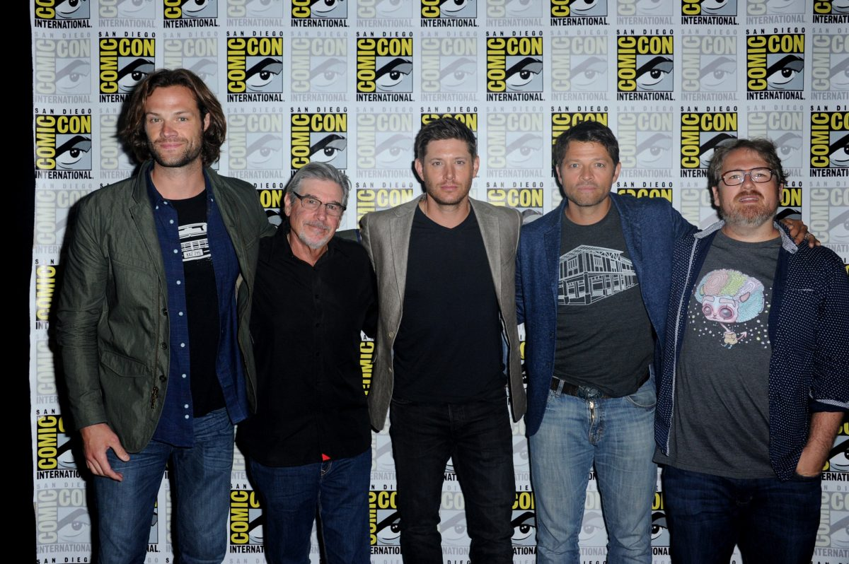 'Supernatural' stars Jared Padalecki, Jensen Ackles, and Misha Collins stand with their arms around writers and producers Robert Singer and Andrew Dabb at Comic-Con