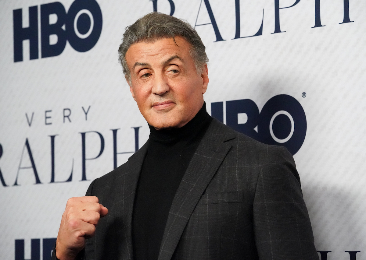 Sylvester Stallone wears a suit and poses on the red carpet