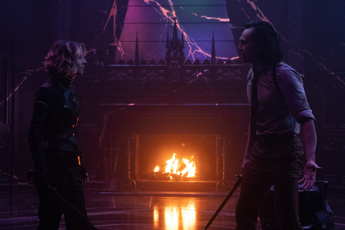 Sophia Di Martino as Sylvie and Tom Hiddleston as Loki in 'Loki' Season 1 Episode 6. They stand across from each other armed with blades. The room is dark and purple and there's a fire burning in the fireplace in the background.