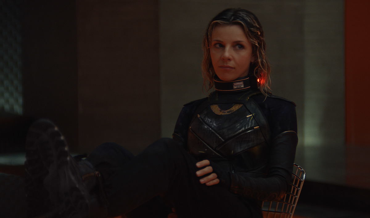Sophia Di Martino in 'Loki' Episode 4. She wears a black and green armored body suit with an electronic band around her neck. Her hair is wet and she has her feet up on a table.