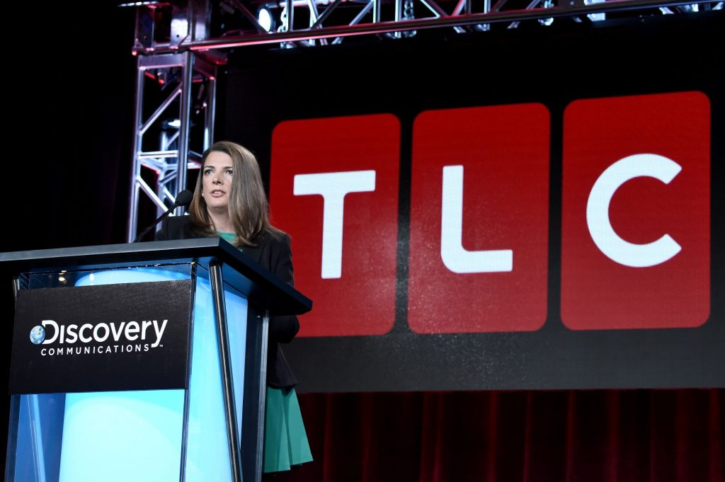 TLC General Manager Nancy Daniels standing in front of a TLC sign speaking at a podium.