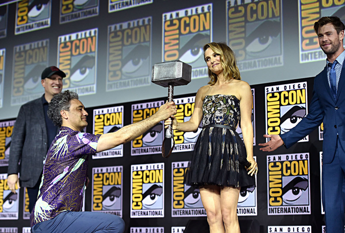 Kevin Feige, Director Taika Waititi, Natalie Portman, and Chris Hemsworth promoting 'Thor: Love and Thunder' San Diego Comic-Con 2019. Waititi is on one knee as he passes Thor's hammer to Portman.