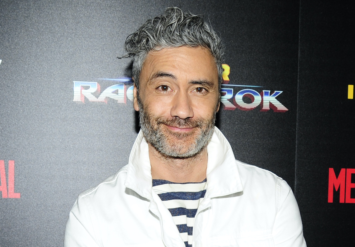 'Thor: Ragnarok' and 'Thor: Love and Thunder' director Taika Waititi smiles in front of a black backdrop that says 'Thor: Ragnarok'