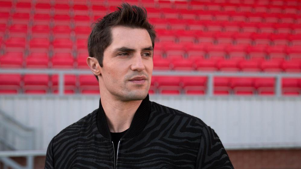 Jamie Tartt stands in front of red stadium seats in 'Ted Lasso'