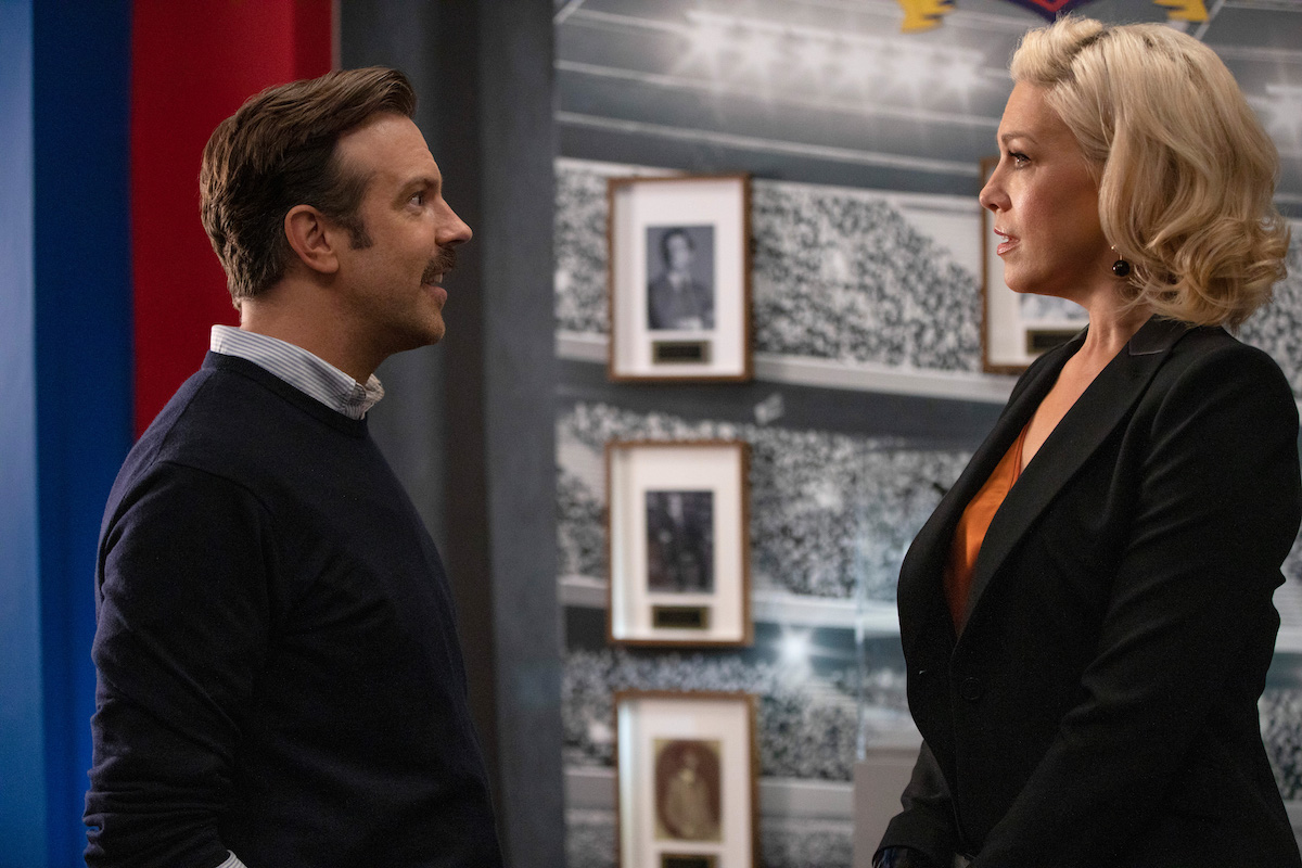 Jason Sudeikis and Hannah Waddingham in 'Ted Lasso' Season 1. Jason stands on the left in a navy blue sweater with a collared shirt underneath. Hannah stands on the right in a black suit and orange top. Their profiles face the camera. A floor-to-ceiling black-and-white photo of a crowded soccer stadium is behind them.