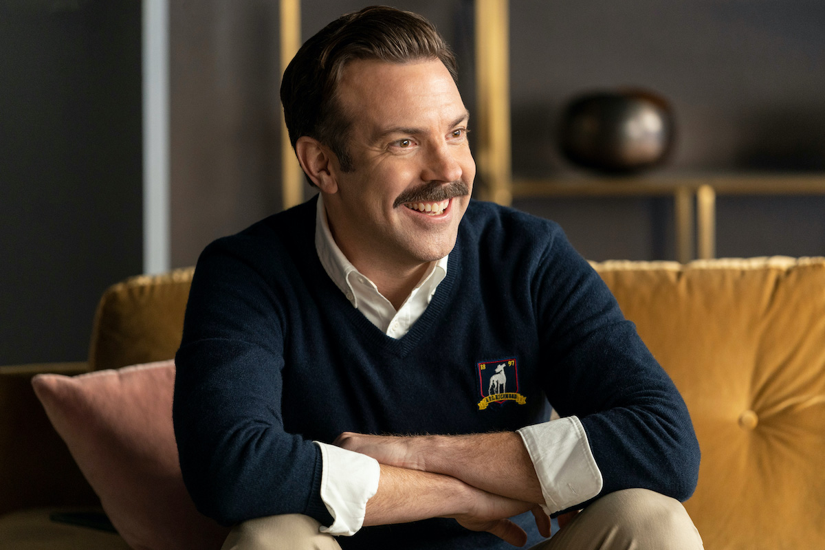 Jason Sudeikis in 'Ted Lasso' Season 2. He sits on a yellow couch with his arms crossed on his knees as he smiles. He wears a navy blue sweater with a white collared shirt underneath. Gold shelves are behind him.