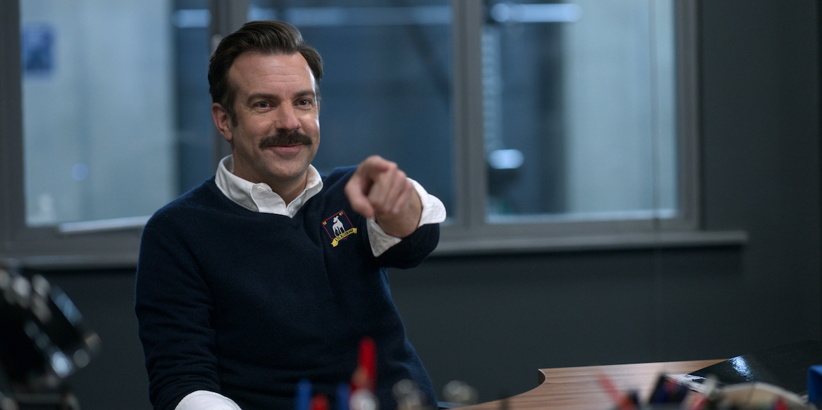 Jason Sudeikis in 'Ted Lasso' Season 2. He sits at a desk with a smirk on his face as he points to someone off camera. He sits in an office in a locker room. There's a window behind him showing the locker room.