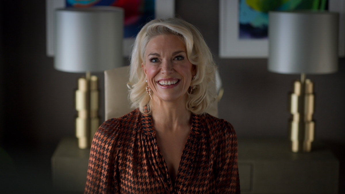 Hannah Waddingham in 'Ted Lasso' Season 2. She smiles in an orange and black houndstooth blouse in an office. Gold lamps and colorful paintings are behind her.