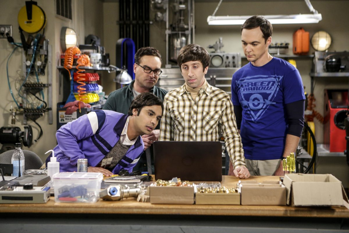 Raj, Leonard, Howard and Sheldon stand around Howard's workstation during an episode of 'The Big Bang Theory'