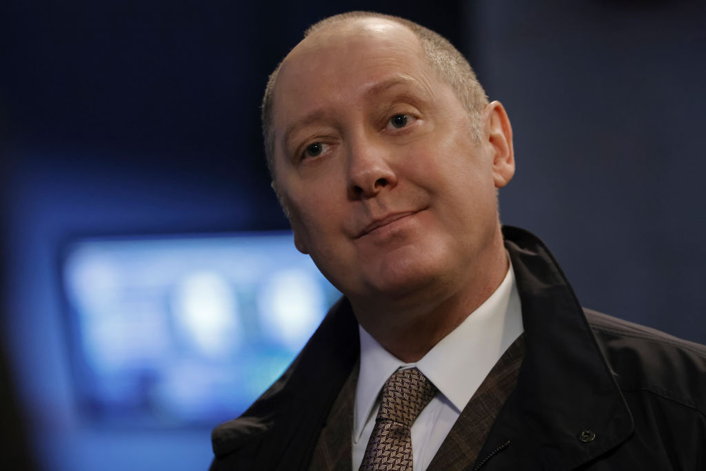 James Spader as Raymond 'Red' Reddington has an annoyed look on his face. He's wearing a suit, tie, and overcoat.
