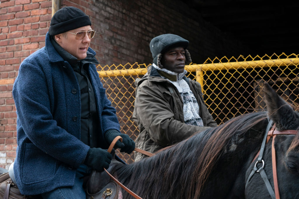Raymond Reddington and Dembe Zuma ride horses net to each other in the brisk air.