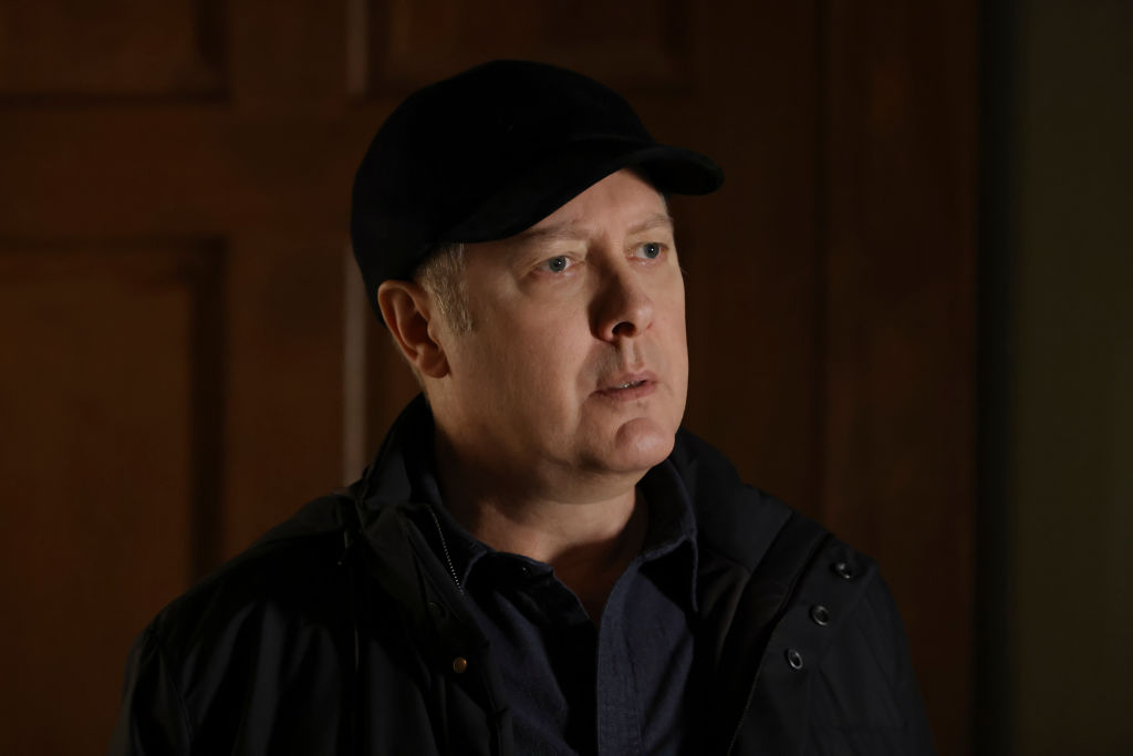 James Spader as Raymond 'Red' Reddington looks concerned. He's wearing a dark jacket and baseball cap.