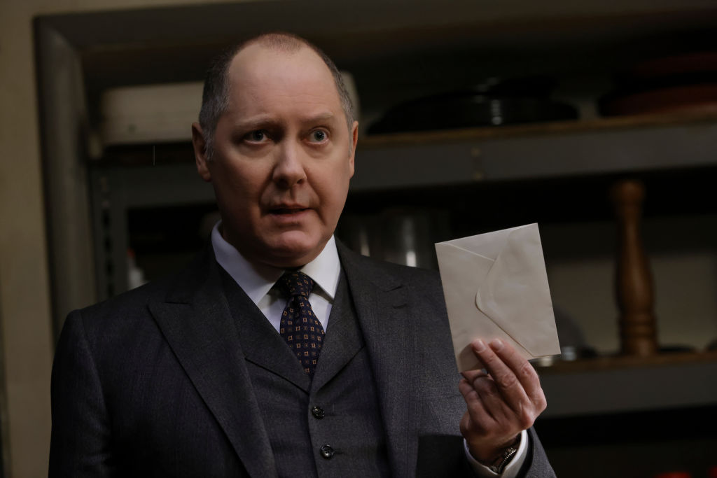 James Spader as Raymond 'Red' Reddington is dressed in a suit and tie. He holds an unopened letter.