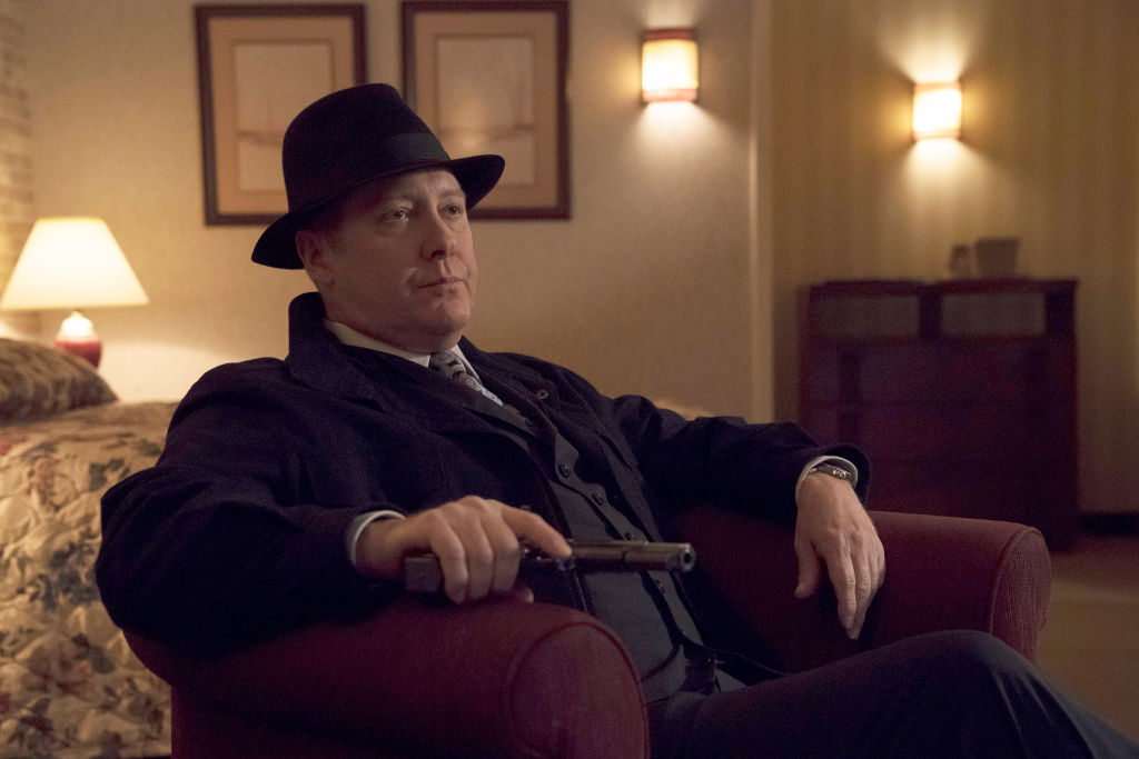 James Spader as Raymond 'Red' Reddington sits in a chair, holding his gun.