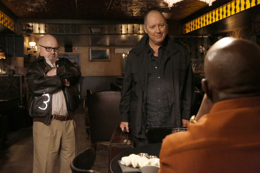 Clark Middleton as Glen Carter and James Spader as Raymond 'Red' Reddington stand in front of a man on the phone.