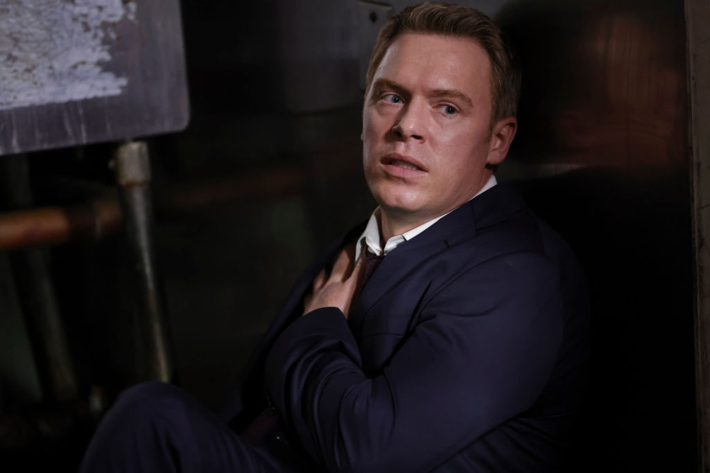 Diego Klattenhoff as Donald Ressler sits on the floor holding a bullet wound on his chest.
