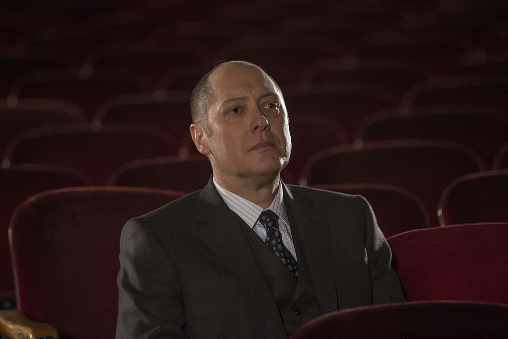 James Spader as Raymond 'Red' Reddington sits in a theater alone.