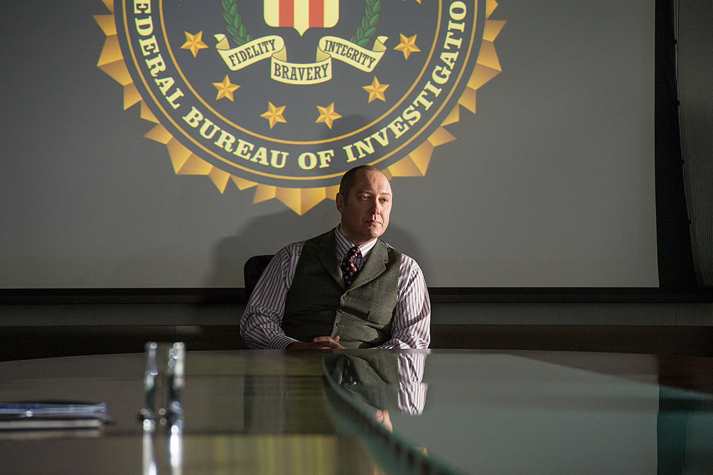 James Spader as Raymond 'Red' Reddington sits in a chair in the FBI headquarters.