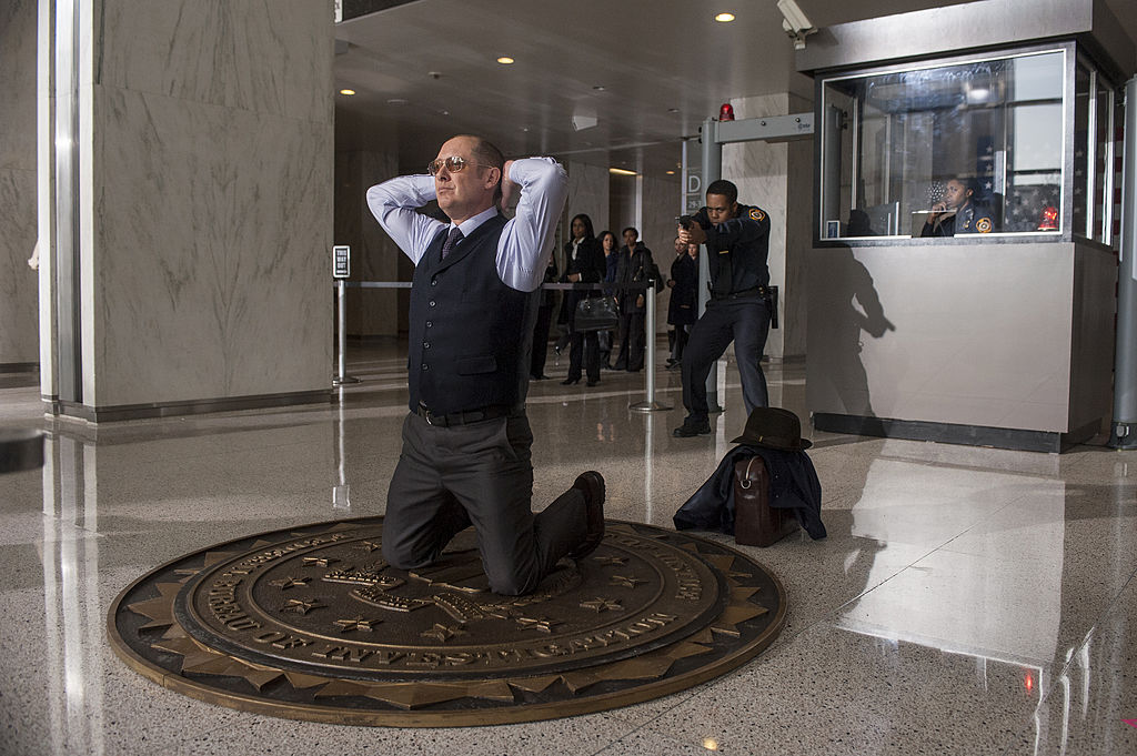 James Spader as Raymond 'Red' Reddington turns himself into the FBI. He's kneeling with his hands behind his head.