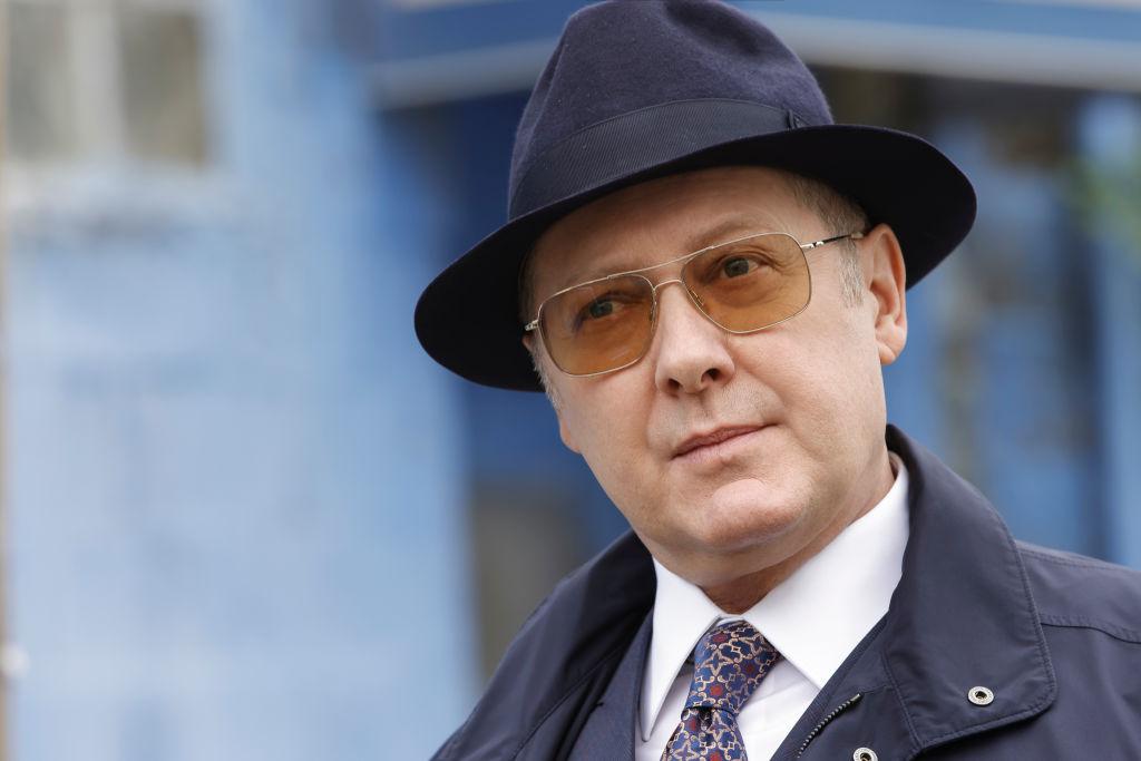 James Spader as Raymond 'Red' Reddington looks on in his trademark fedora and sunglasses.