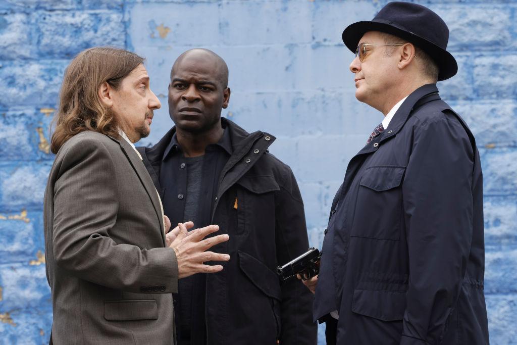 Walter Stevens holds up his hands as Dembe Zuma watches Raymond 'Red' Reddington point a gun at Watler.