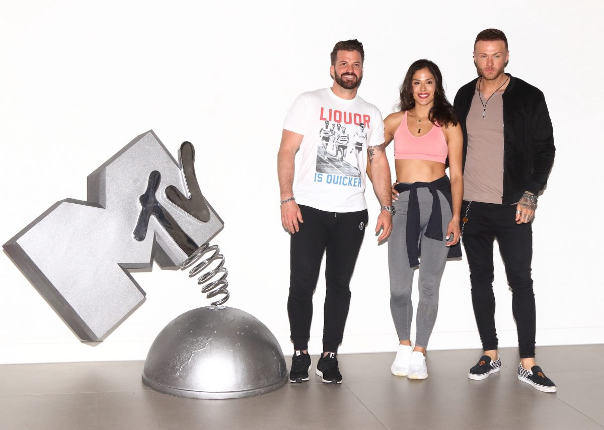 Johnny 'Bananas' Devenanzio, Nany Gonzalez, and Kyle Christie from MTV's 'The Challenge' standing next to a large MTV statue