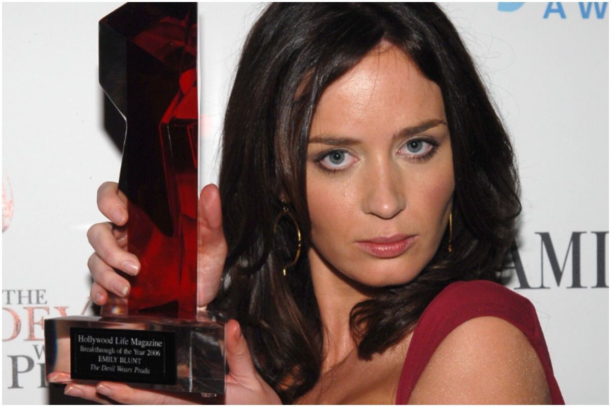 The Devil Wears Prada: Emily Blunt holding an award while wearing a red dress for her role as Emily.