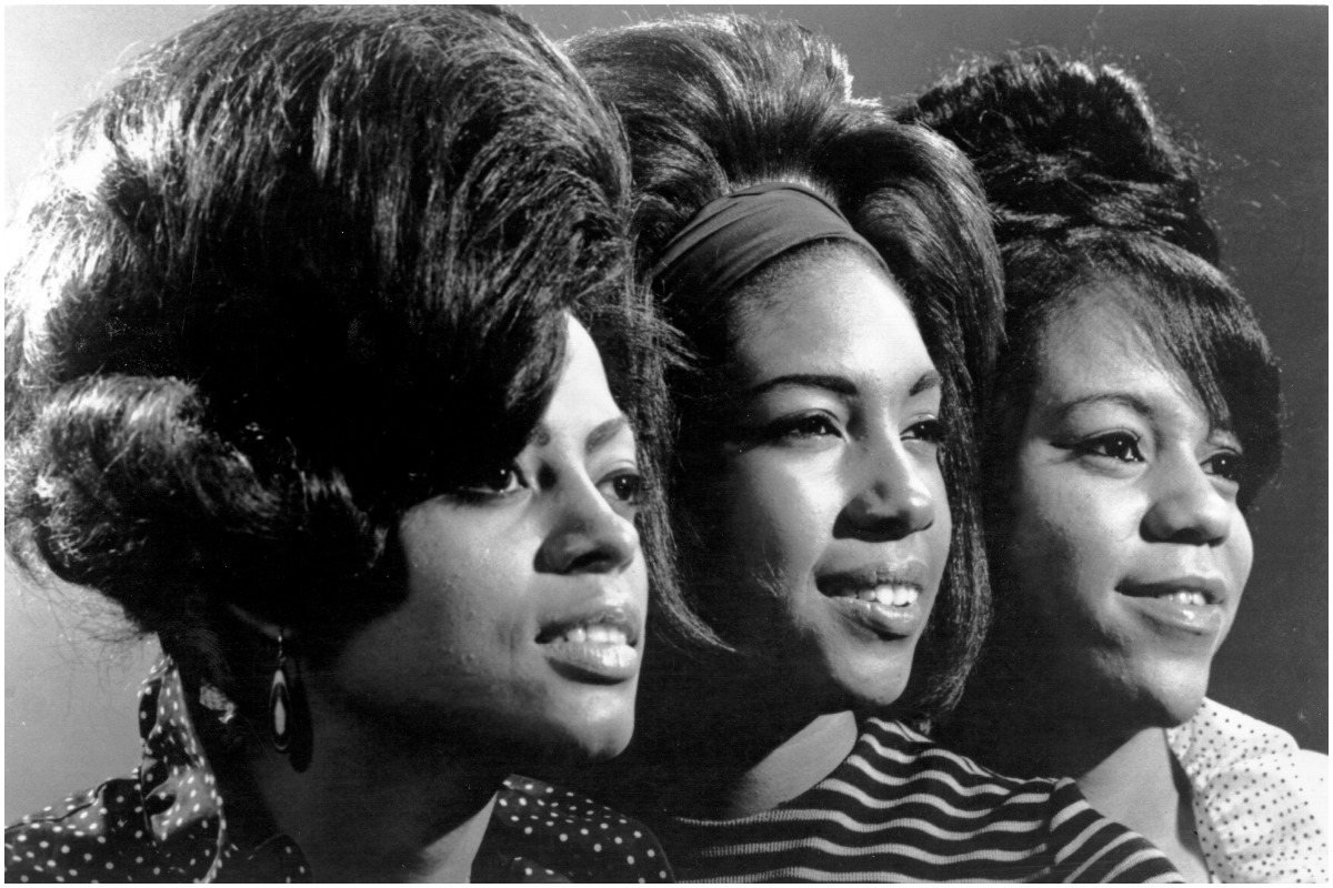 The Supremes: Diana Ross, Mary Wilson, and Florence Ballard smiling in a black and white photo.