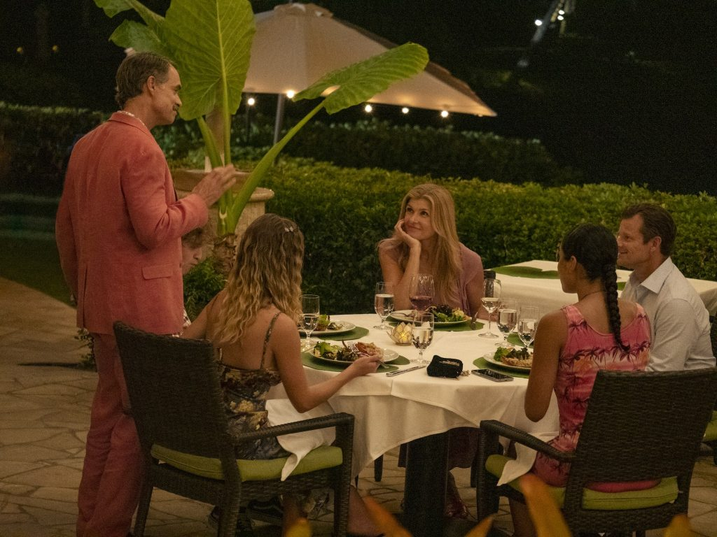 Some of the White Lotus cast sits around a table at the resort for dinner