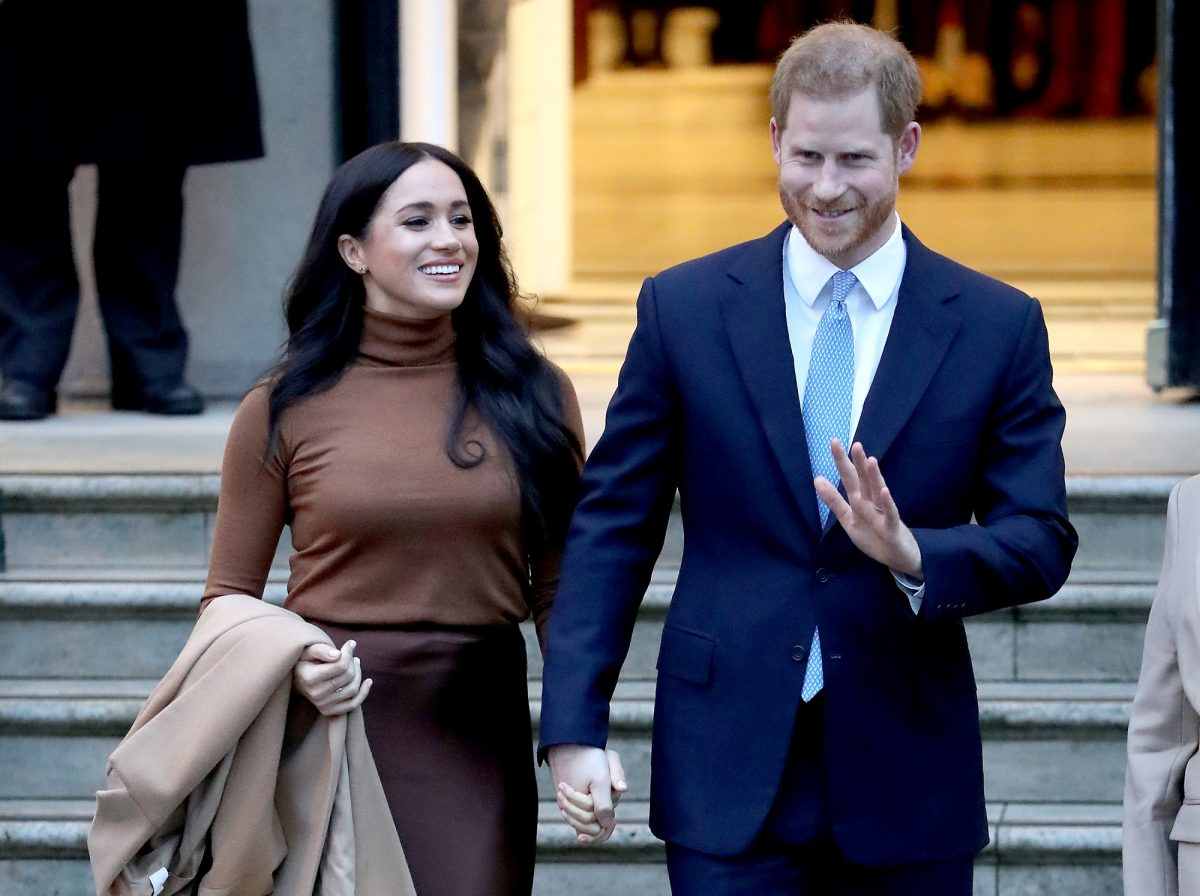 Meghan Markle wears a brown outfit holding hands with Prince Harry in a suit