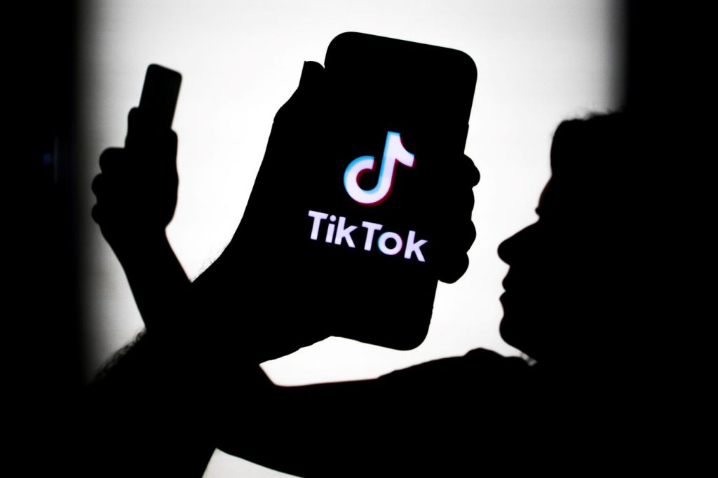 Shadows of a person holding a phone out in front of their face with their arm crossed with a closeup picture of a shadow of a hand holding a phone with the Tik Tok logo on it all against a white background.